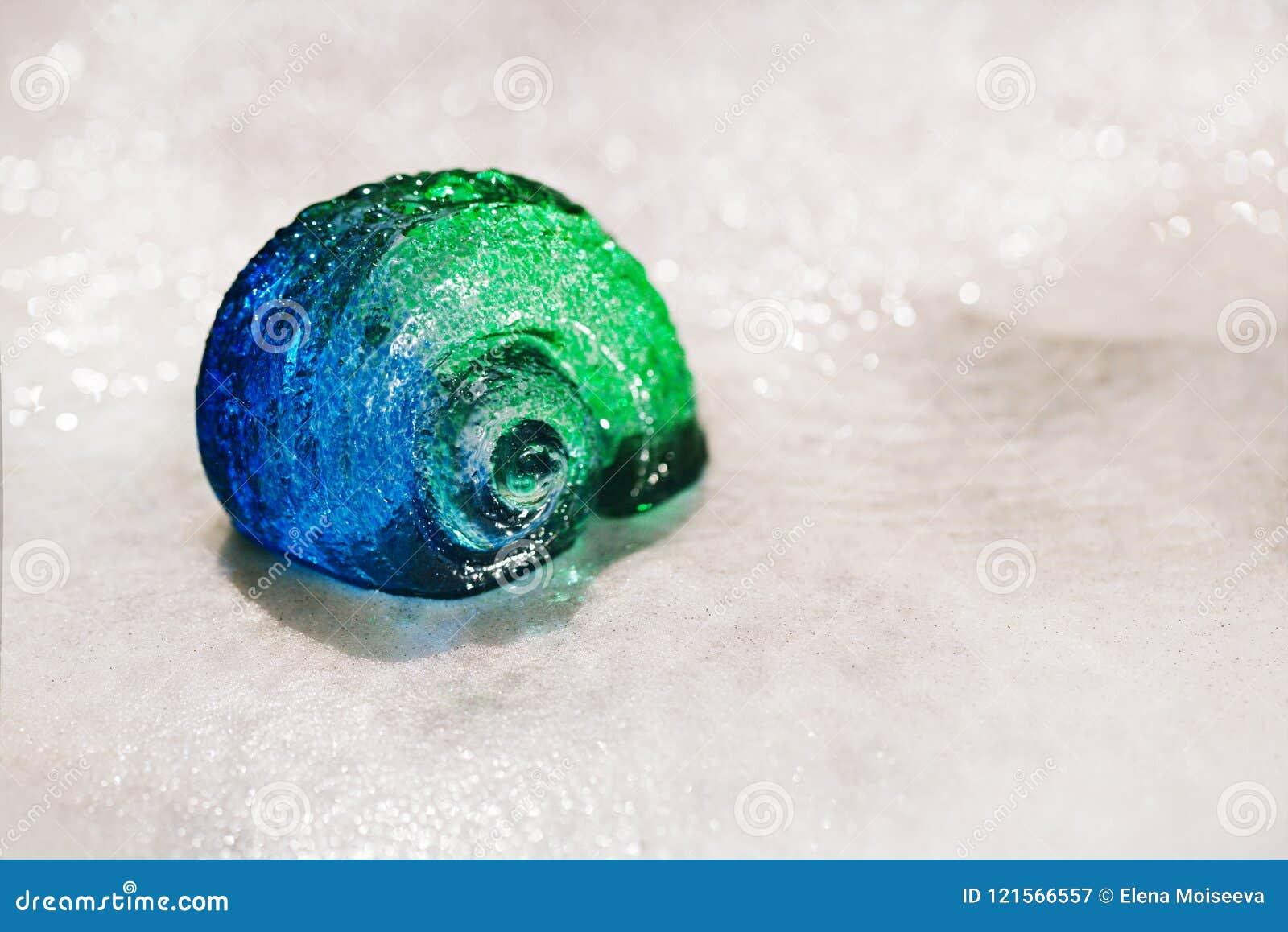 大在蓝色小卵石的扇贝玻璃海壳在水滴下