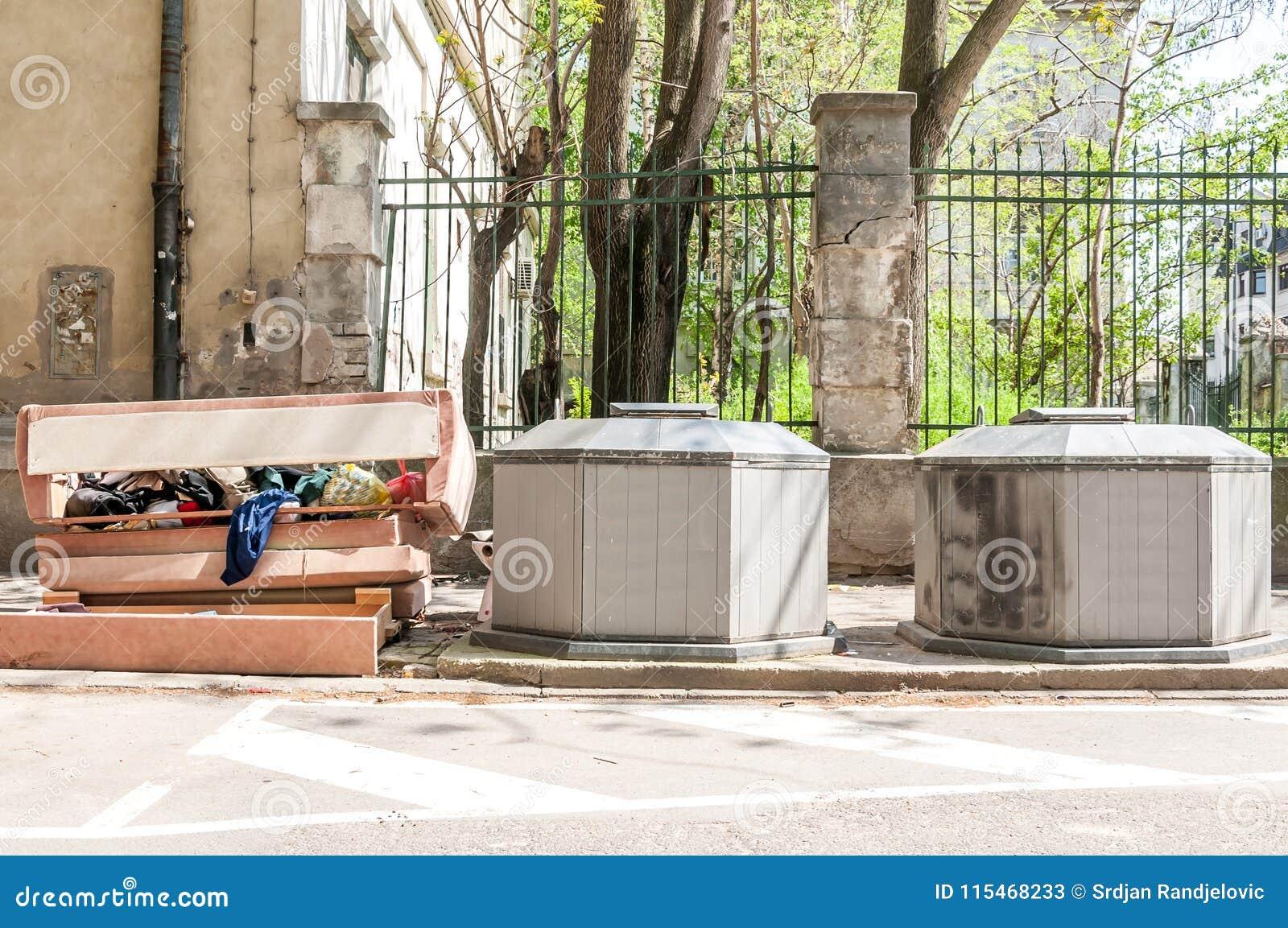大堆垃圾和破烂物在街道倾销了在两个地下大型垃圾桶罐头附近