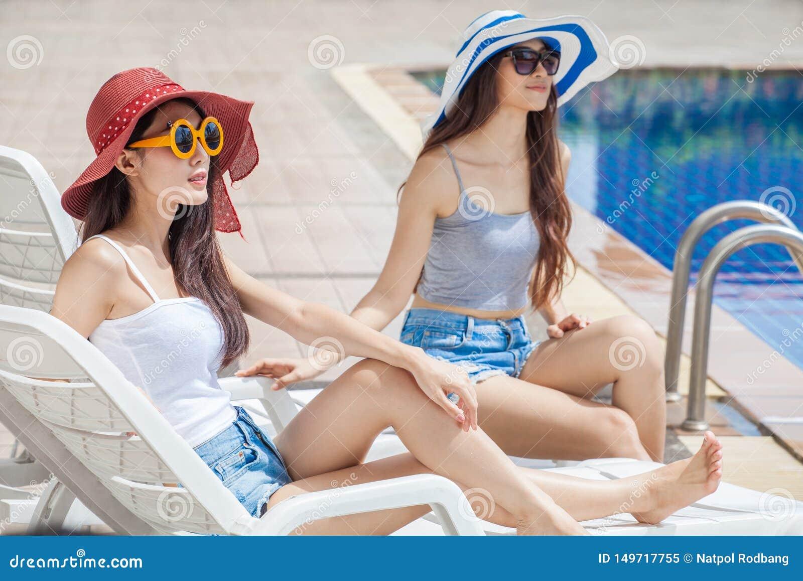 大夏天帽子和太阳镜的两名美丽的年轻亚裔妇女坐一起sunbed由游泳场 E
