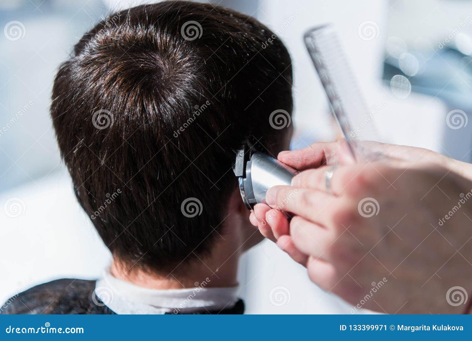 大师在理发店剪人,美发师的头发做一个年轻人的发型