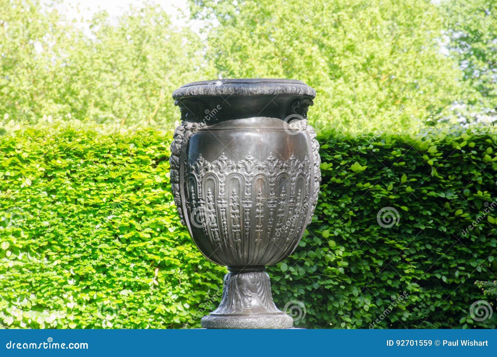 大希腊样式花瓶在有树篱的规则式园林里