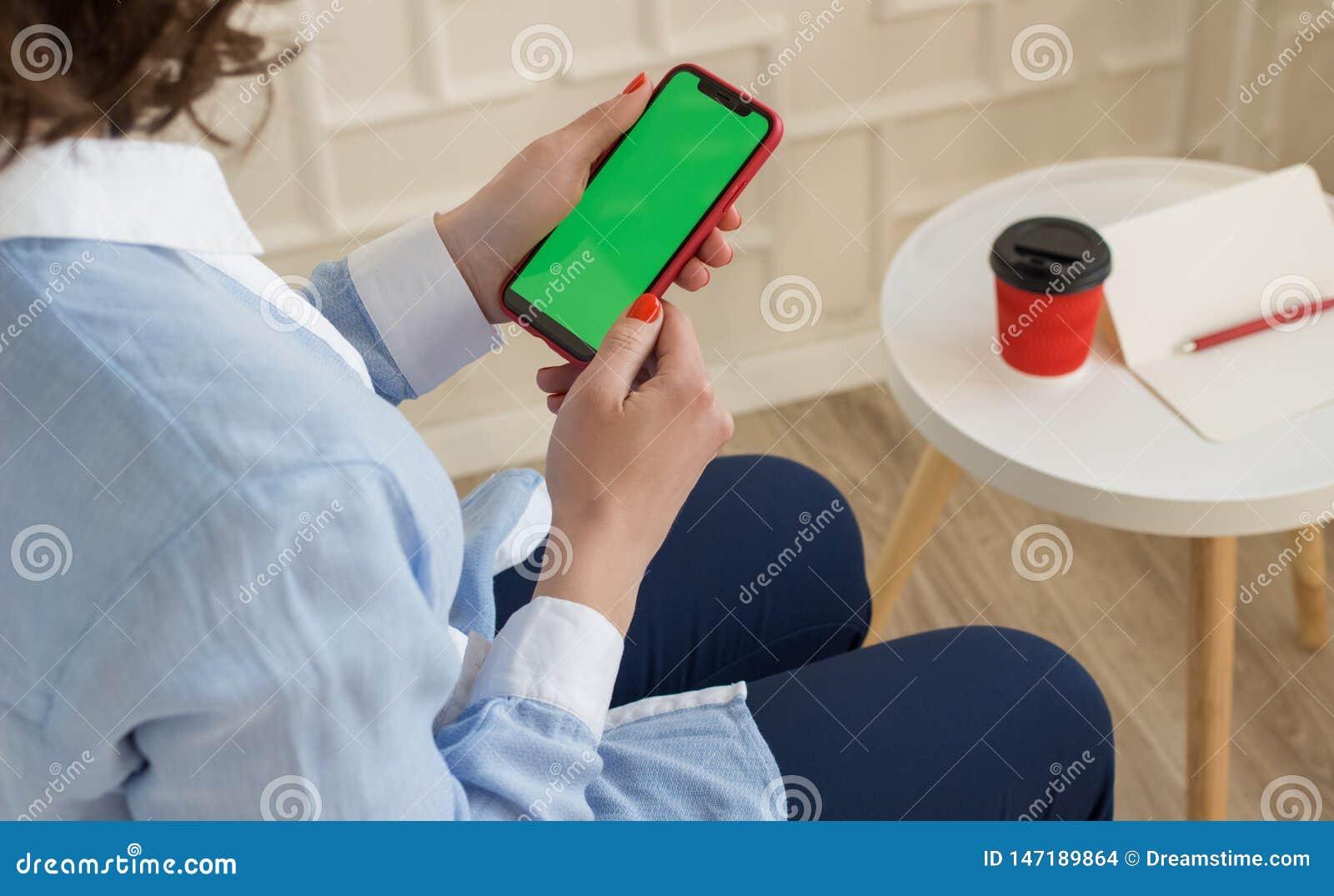 大模型图象:女孩蓝色拿着有色度关键屏幕的衬衣和长裤的黑手机