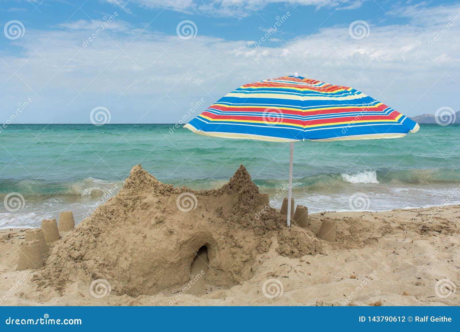 大沙堡和伞在海滩与海在背景中
