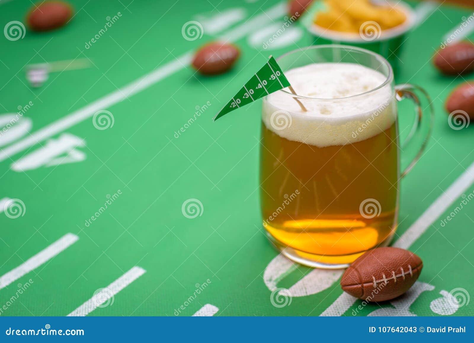 大玻璃杯子在桌上的冰镇啤酒与superbowl党装饰