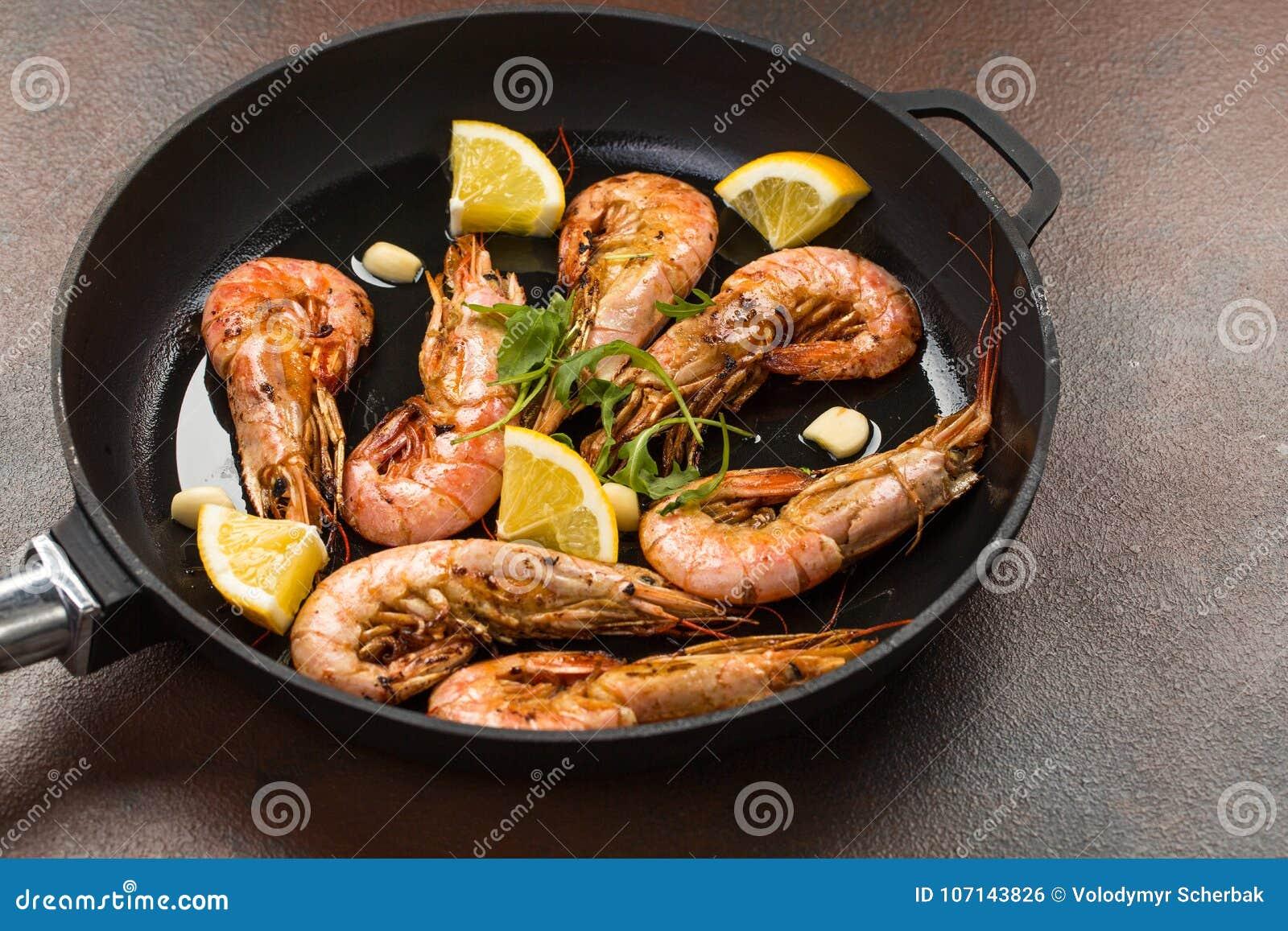 大虾虾用大蒜、柠檬、香料和意大利欧芹在白色被绘的土气木头,选择的焦点的一个黑平底锅装饰,