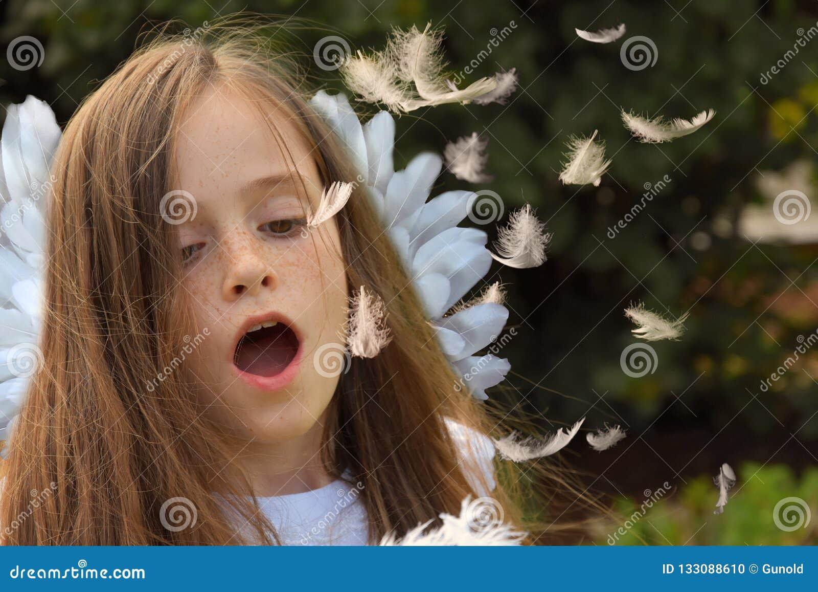 天使飞行羽毛的服装打击的十几岁的女孩