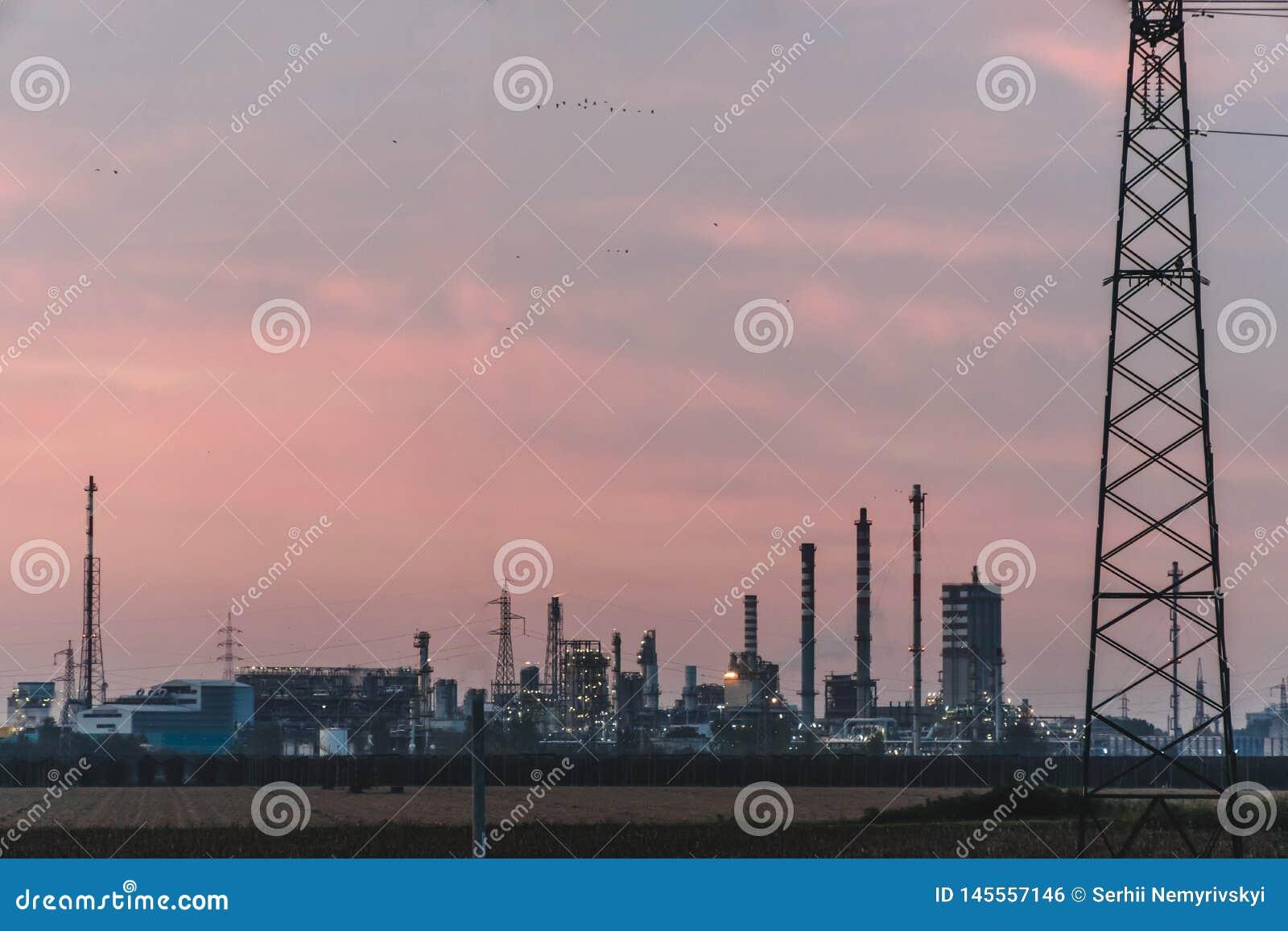 天空日落背景的,有平衡背景的天空的石油化工厂工业工厂 在现代的意大利北部工作