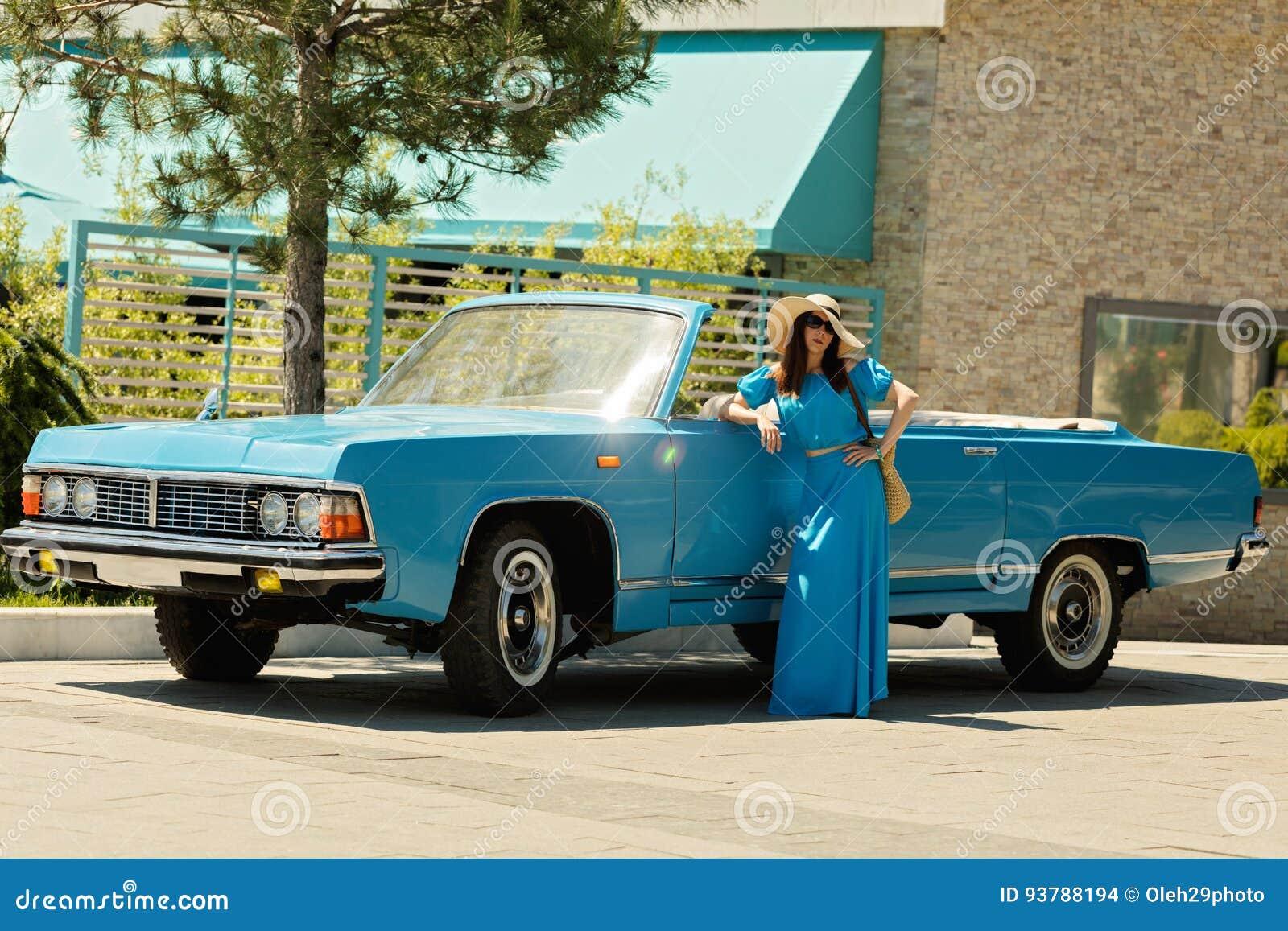 天蓝色的长的礼服的年轻美丽的妇女在一辆减速火箭的汽车附近
