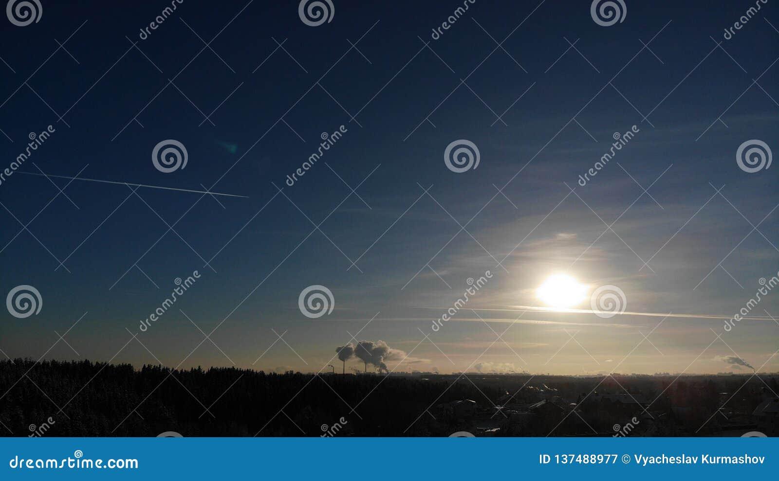 太阳发光烟的一清楚的冷淡的天从发电站的管子上升概略的看法 俄罗斯圣彼德堡reg