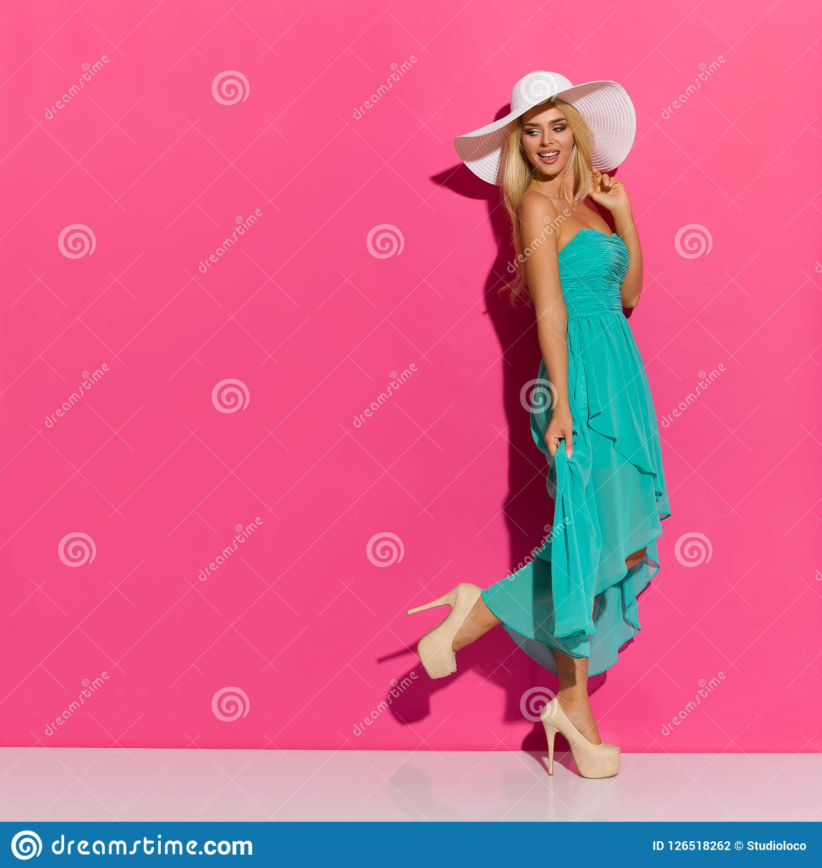 太阳帽子、绿松石礼服和高跟鞋的走的美丽的白肤金发的妇女