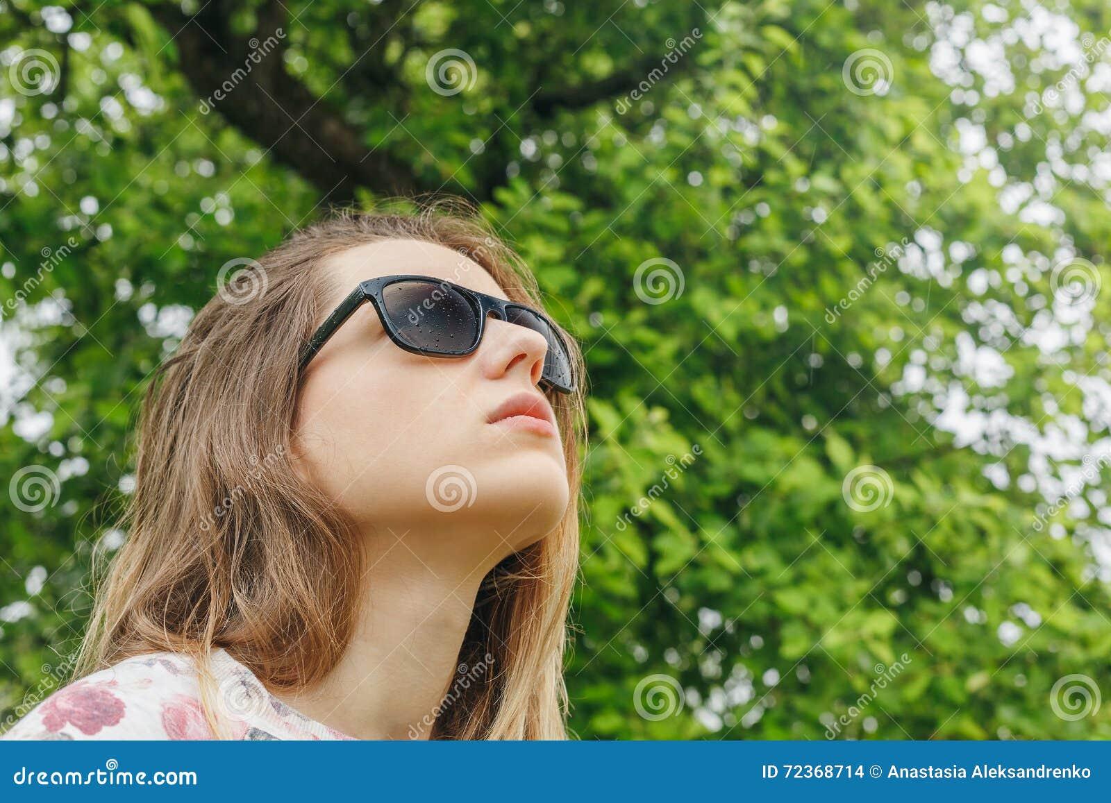 太阳镜的女孩下雨看天空