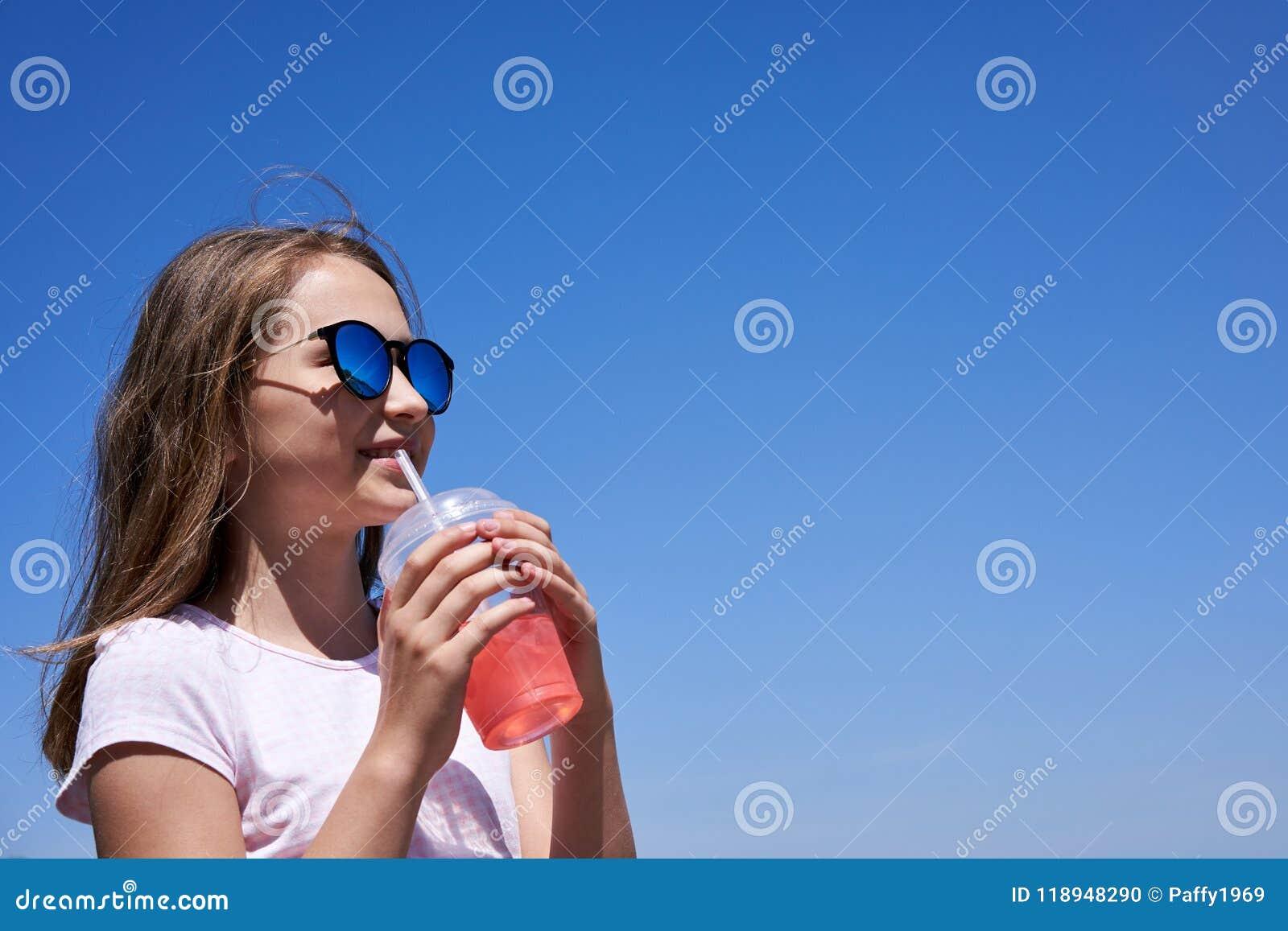 太阳镜的女孩喝冷的柠檬水的