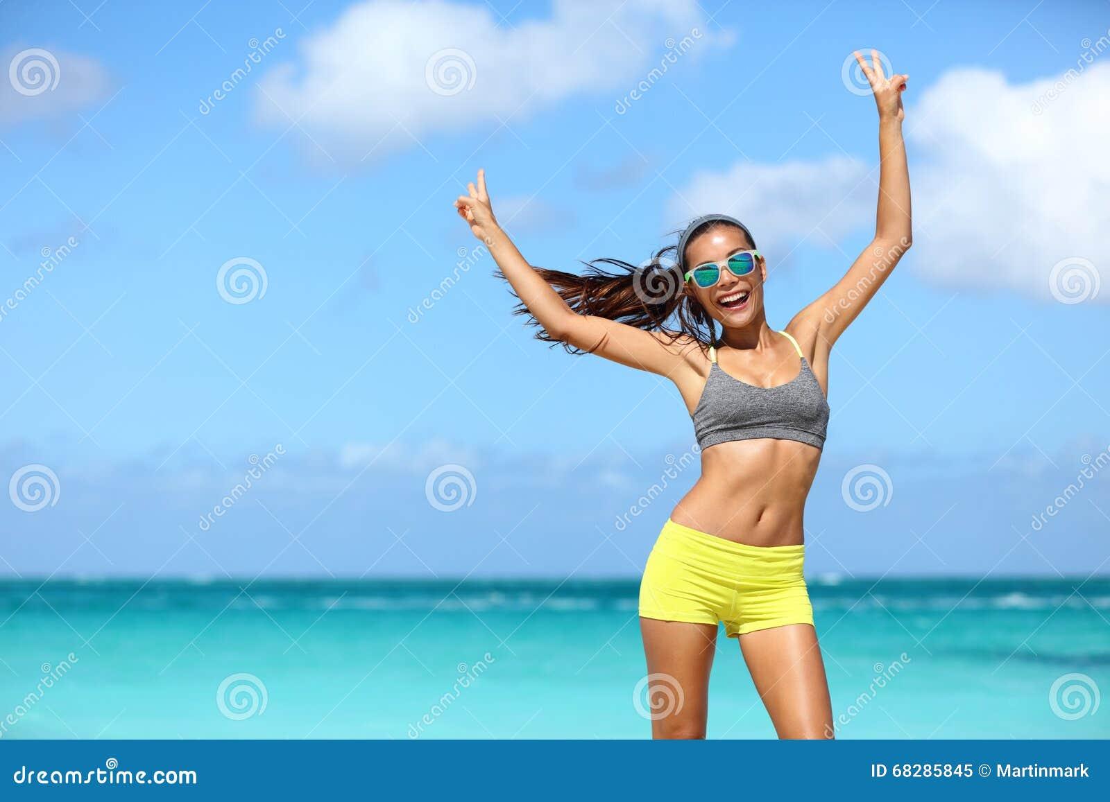 太阳镜的愉快的快乐的健身妇女赢取胳膊的做v手签字
