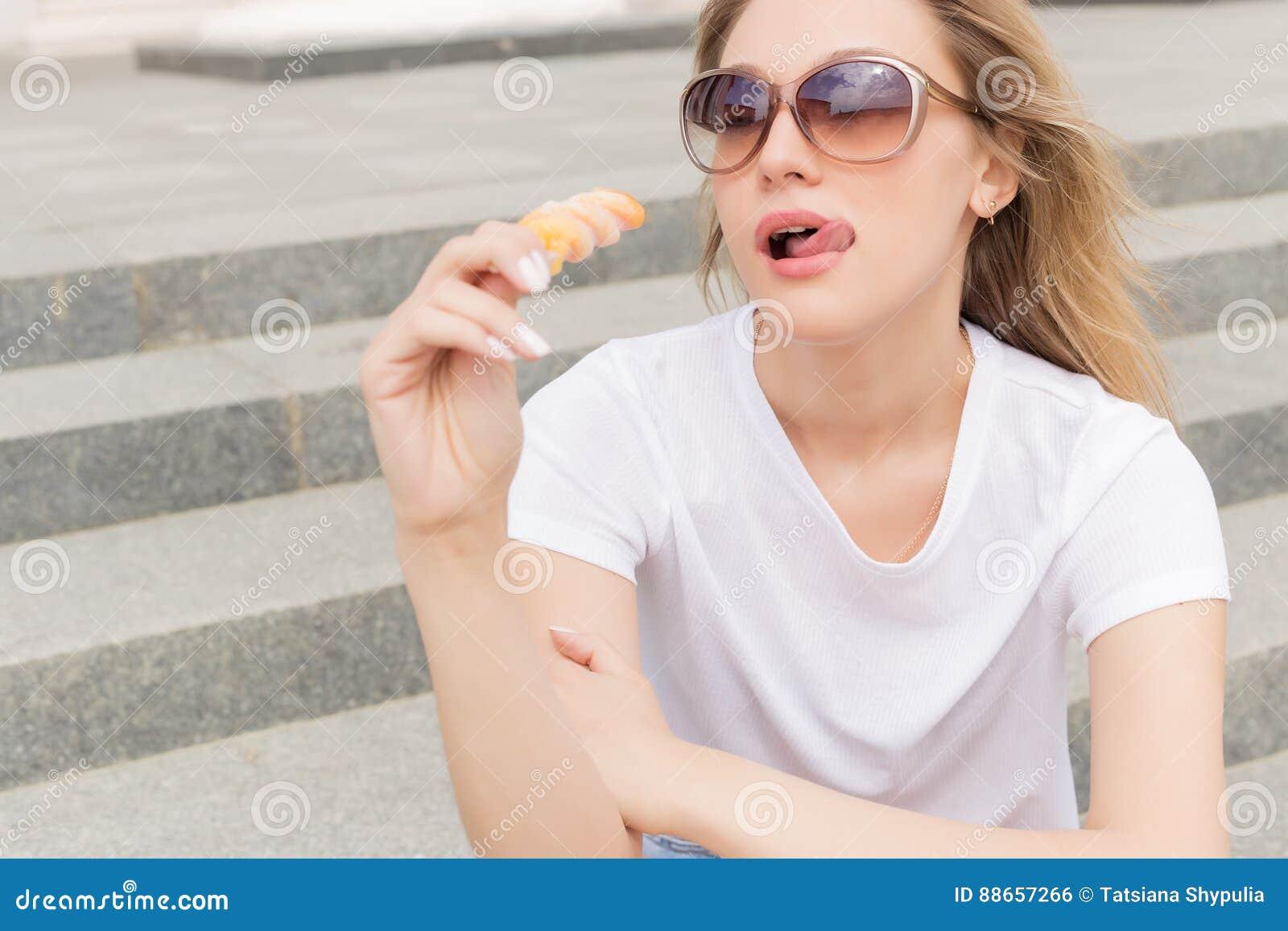 太阳镜的美丽的年轻性感的女孩吃在梯子的冰淇凌和舔肥满嘴唇的每明亮的晴朗的热的天