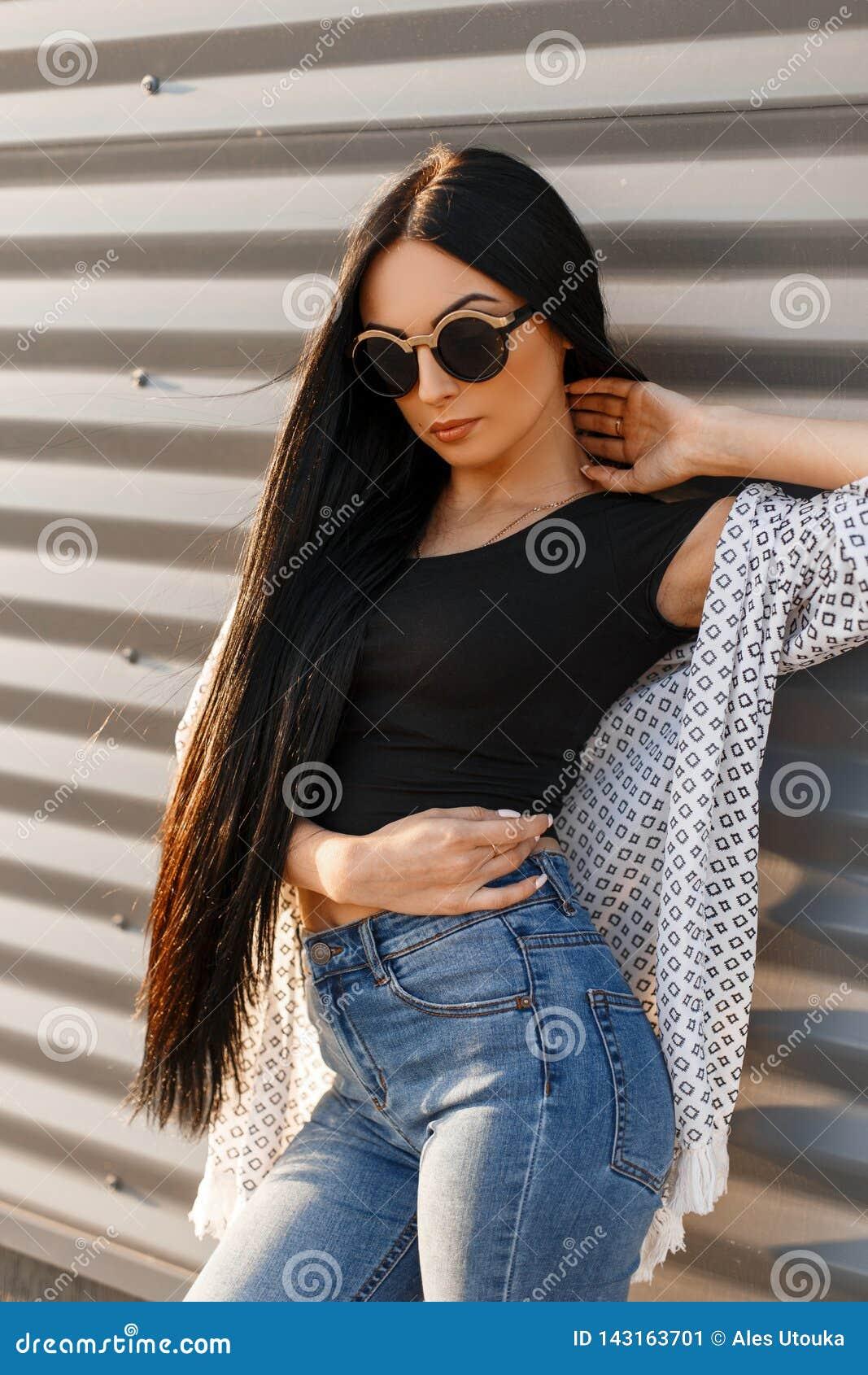 太阳镜的美国俏丽的性感的年轻行家妇女有在一件时髦的T恤杉的长发的在时髦牛仔裤的一件夏天夹克