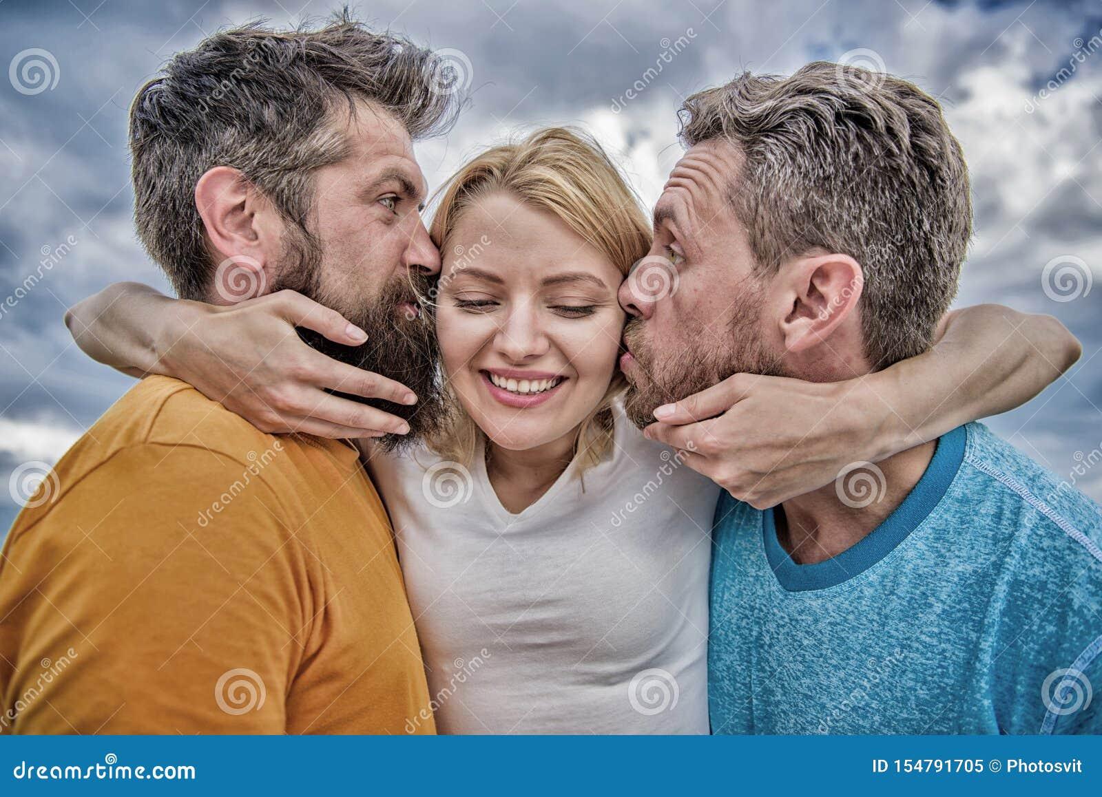 夫人享受浪漫联系两位钦佩者 她喜欢男性关注 三角爱 人亲吻同样女孩面颊 ??