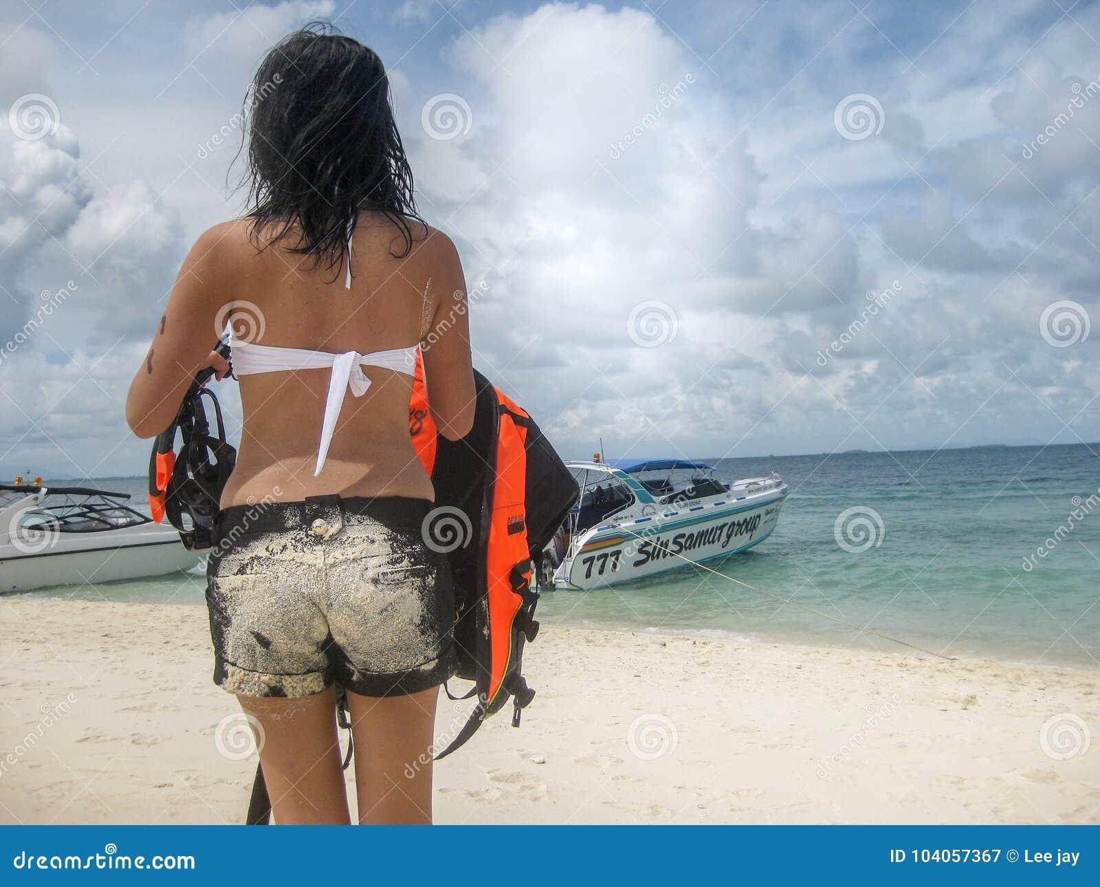 夫人在海滩旅行的后侧方步行在泰国