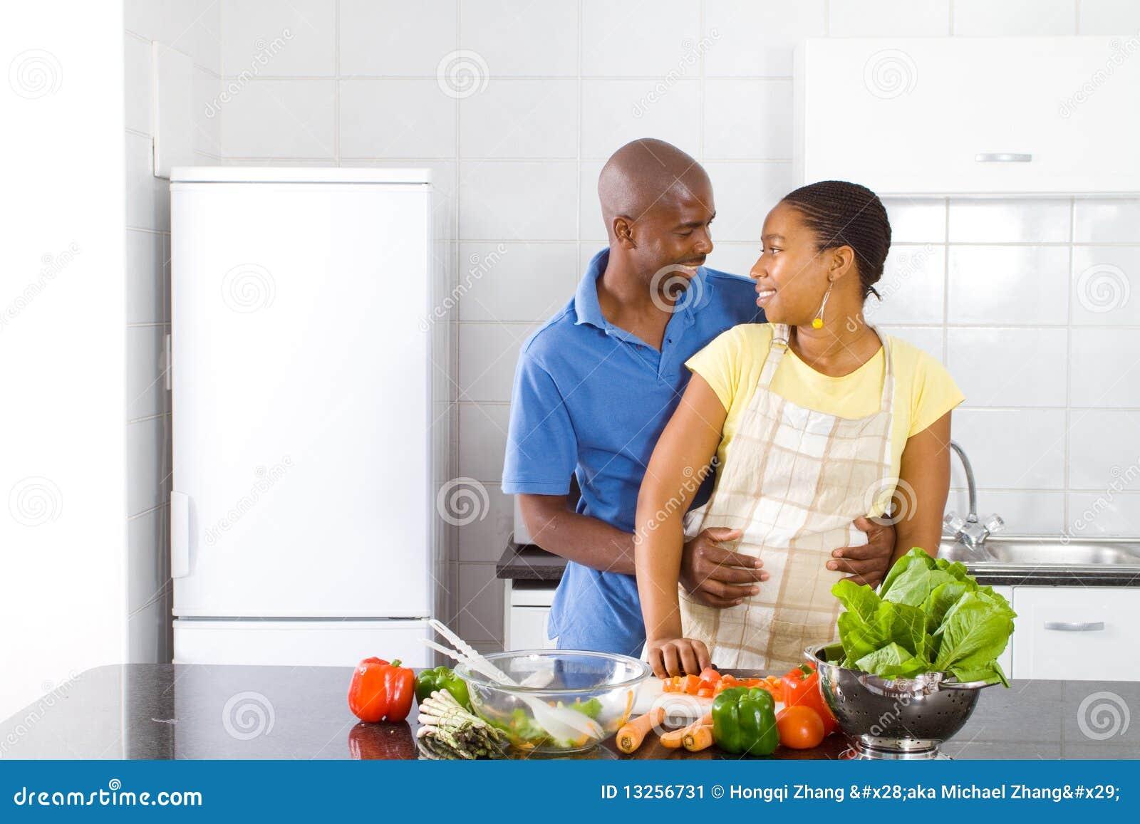 非洲裔美国人的夫妇愉快的拥抱的亲密的亲吻的厨房.图片