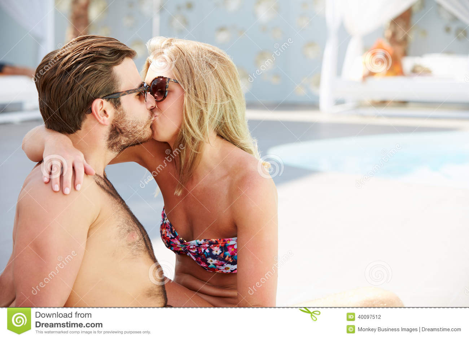 年轻夫妇在度假放松由游泳池的