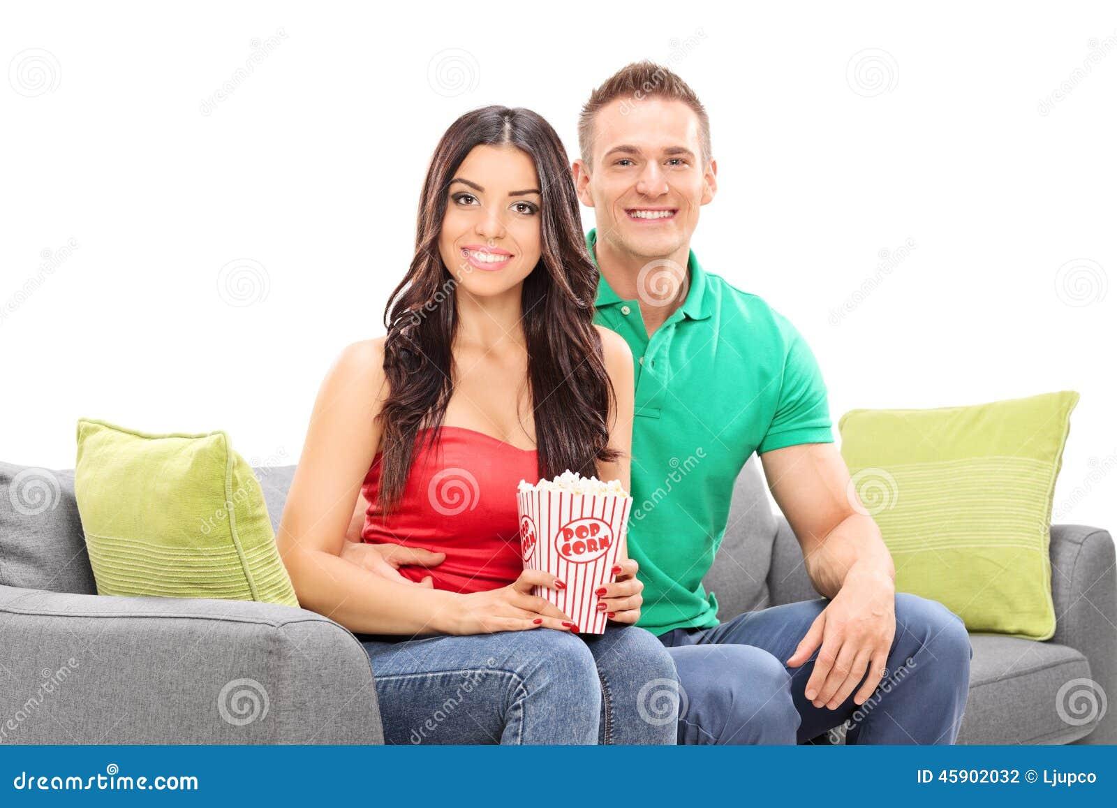 年轻夫妇坐有箱的长沙发玉米花