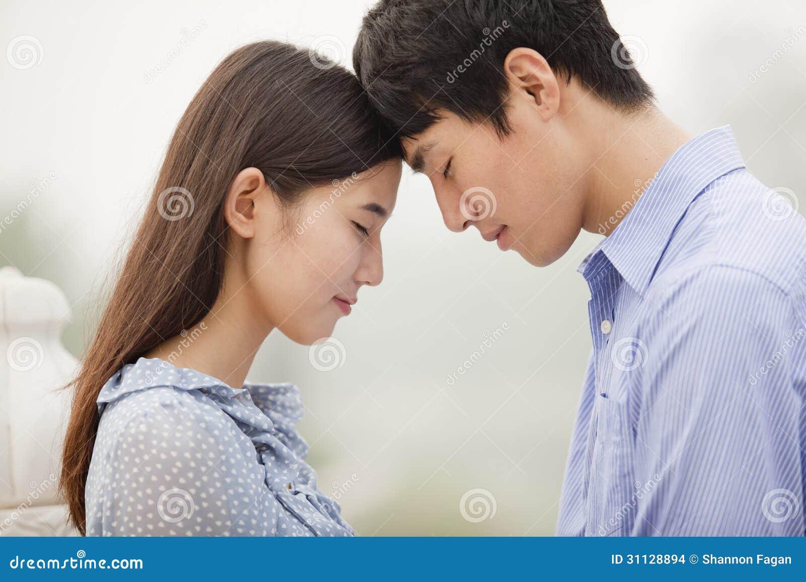 年轻夫妇感人的前额,在爱