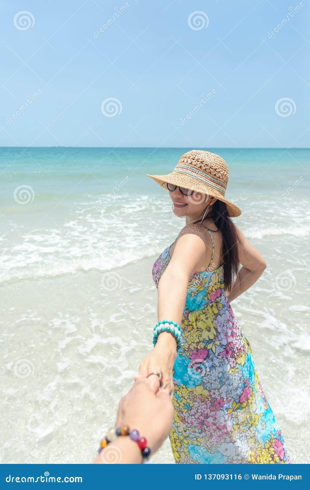 夫妇暑假旅行,走在浪漫蜜月的妇女和放松在沙滩在握男朋友f的手的假日