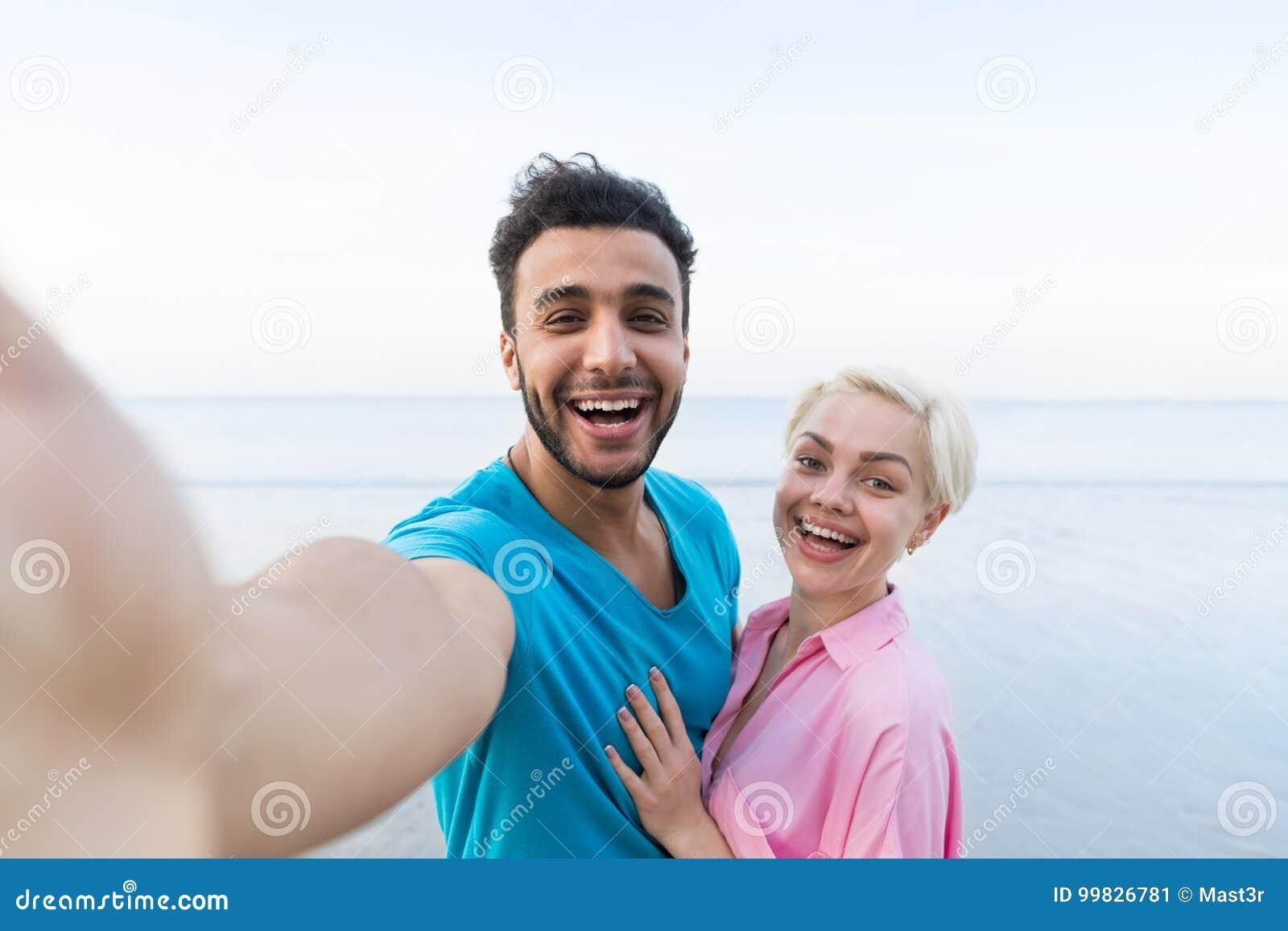 夫妇海滩暑假,拍Selfie照片,人妇女容忍海的美丽的年轻愉快的人民