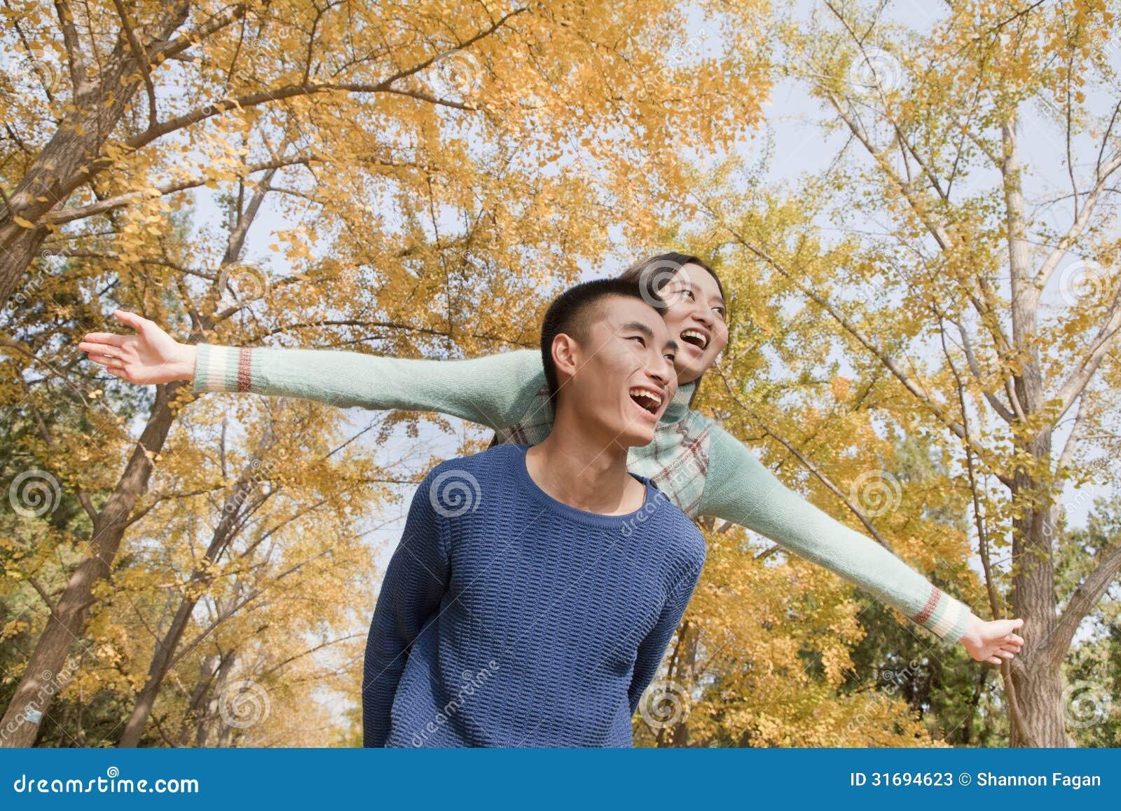 年轻夫妇肩扛在公园