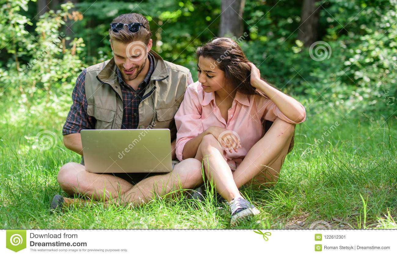夫妇青年时期花费休闲户外与膝上型计算机 现代技术给在其中任一的机会是网上和工作