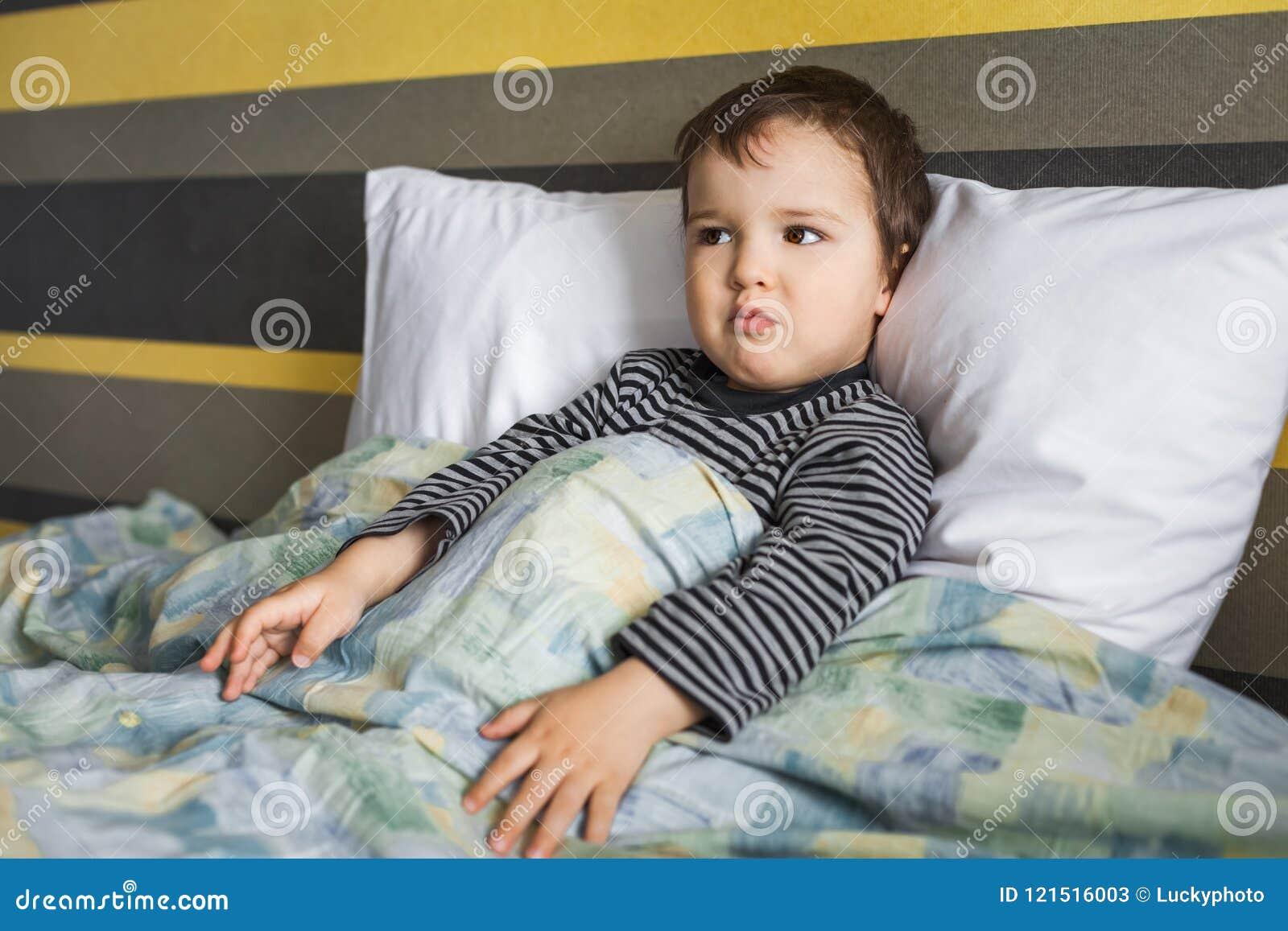 失望的病的儿童男孩坐床