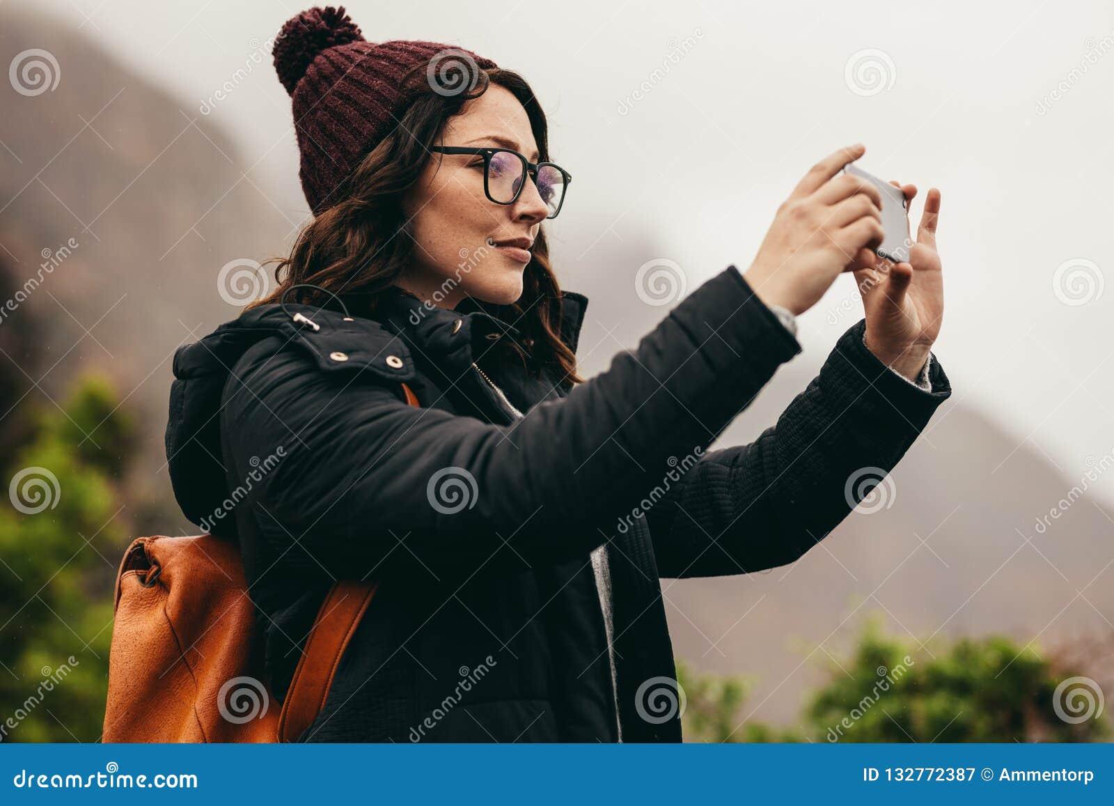 夺取在她的电话的女性游人风景