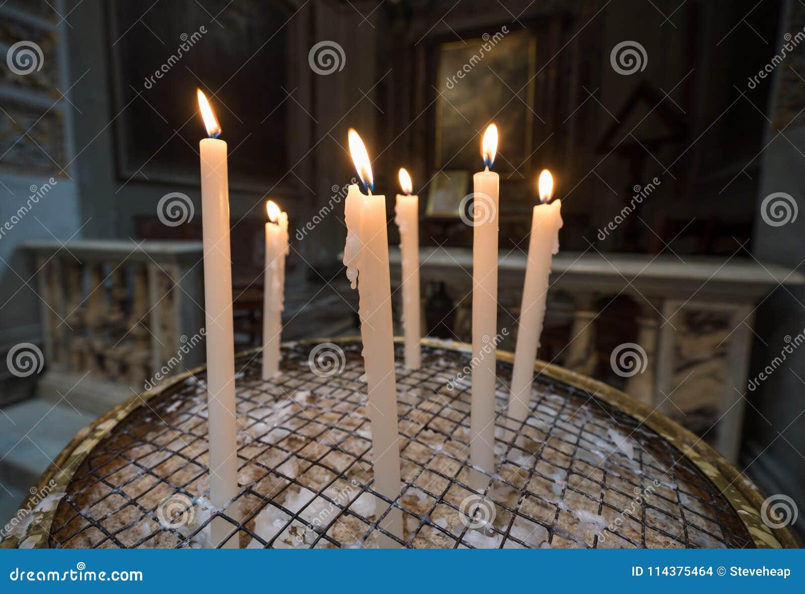 奉献或祷告蜡烛在天主教堂里