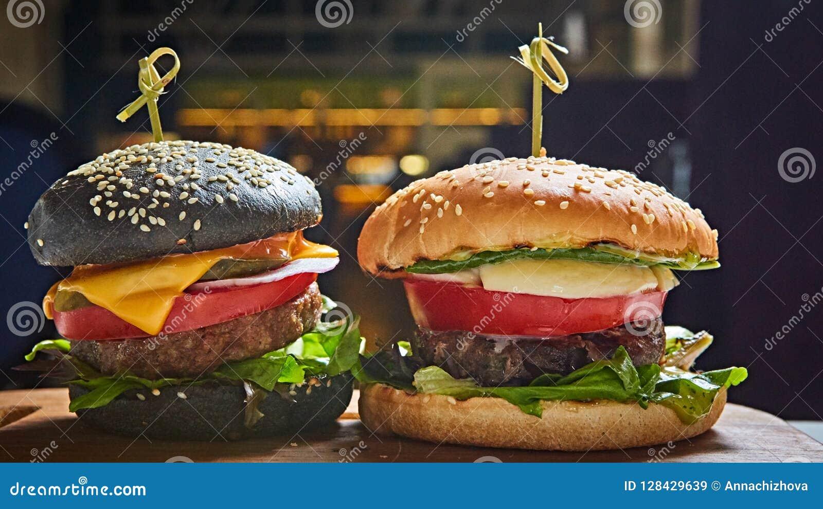 套在黑白小圆面包的自创汉堡用蕃茄,莴苣,乳酪,在木服务板的葱在黑暗