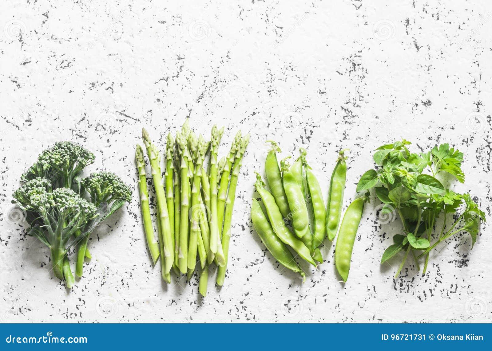 套新鲜的有机绿色菜-硬花甘蓝,绿豆,芦笋,在轻的背景的牛至 食物背景,顶视图