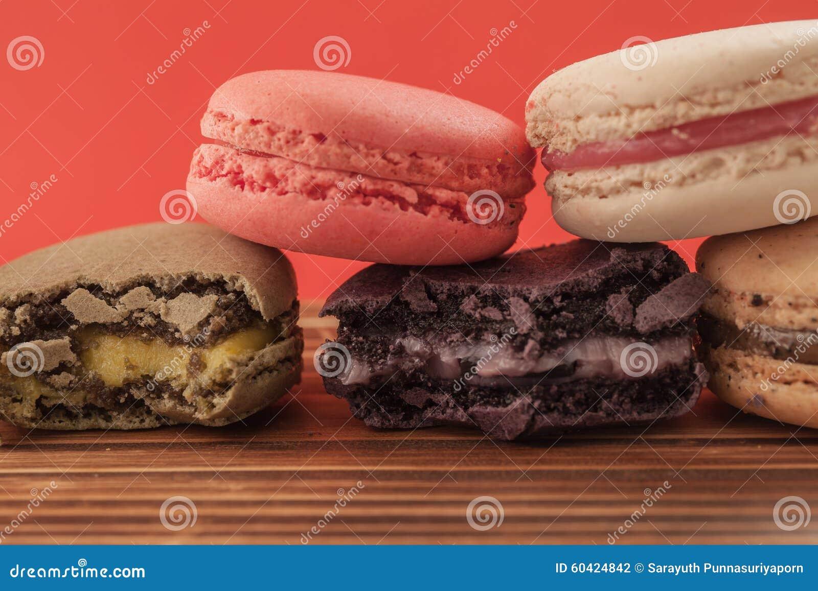 套macarons以在木桌上的各种各样的颜色在红色柔和的淡色彩是