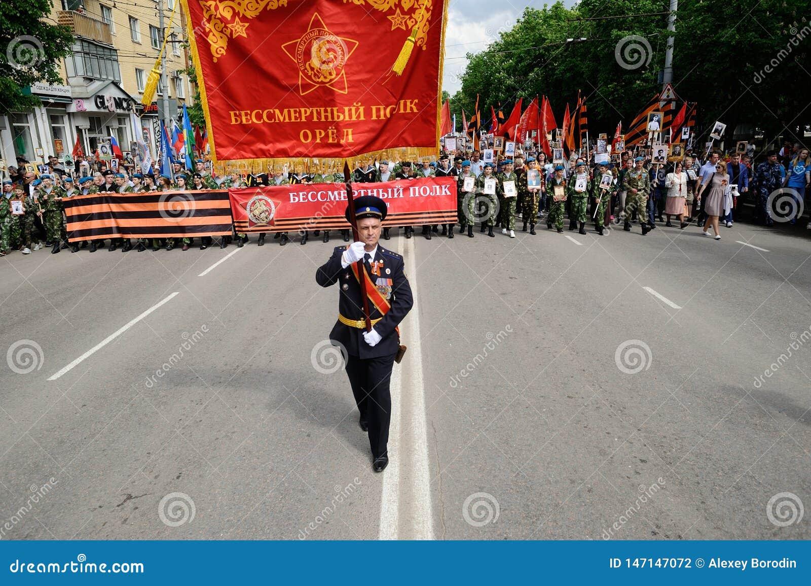 奥勒尔号,俄罗斯,2019年5月09日:胜利天,不朽的军团游行 有红旗的官员前进在人面前巨大的人群的
