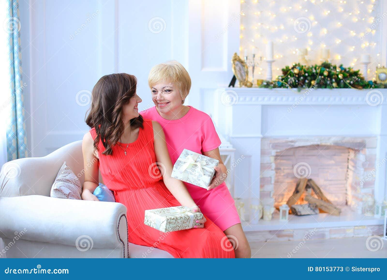 女儿和母亲一起坐长沙发,微笑对每个o