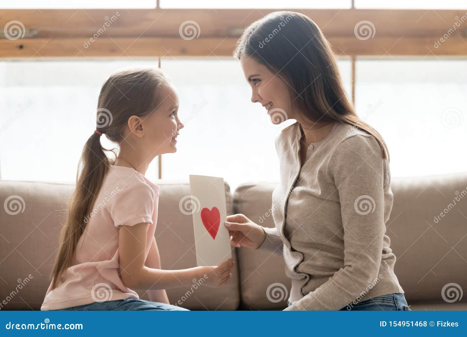 女儿和母亲坐拿着手工制造明信片的长沙发