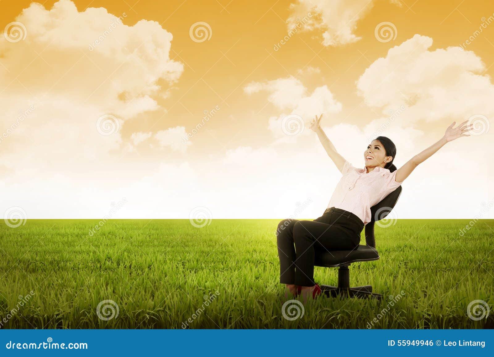 女商人坐在草甸的椅子