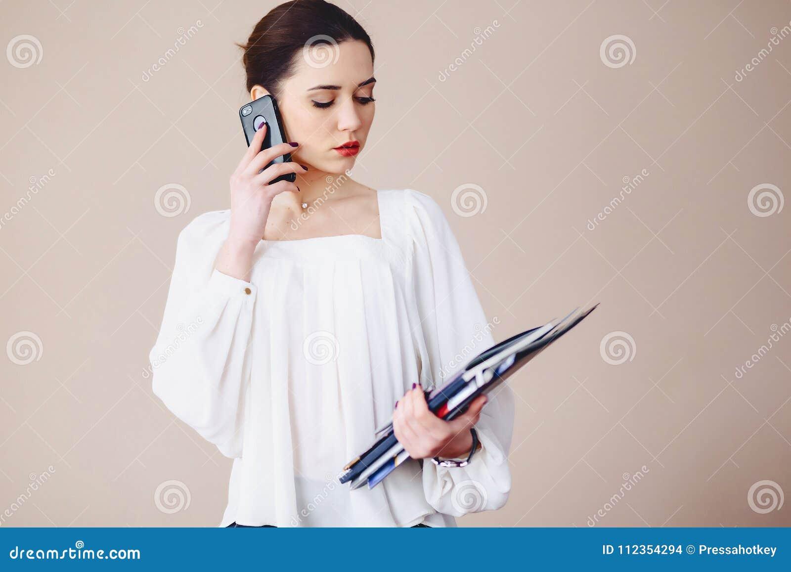 女商人谈话在有文件的电话在她的手上