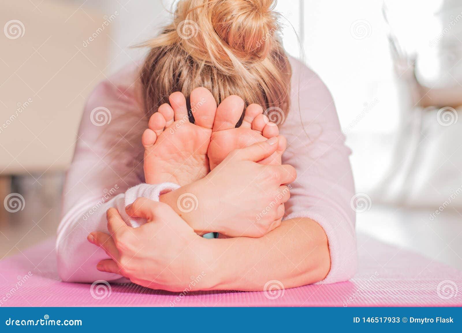 女子实践的瑜伽,今后供以座位的弯姿势,做paschimottanasana锻炼