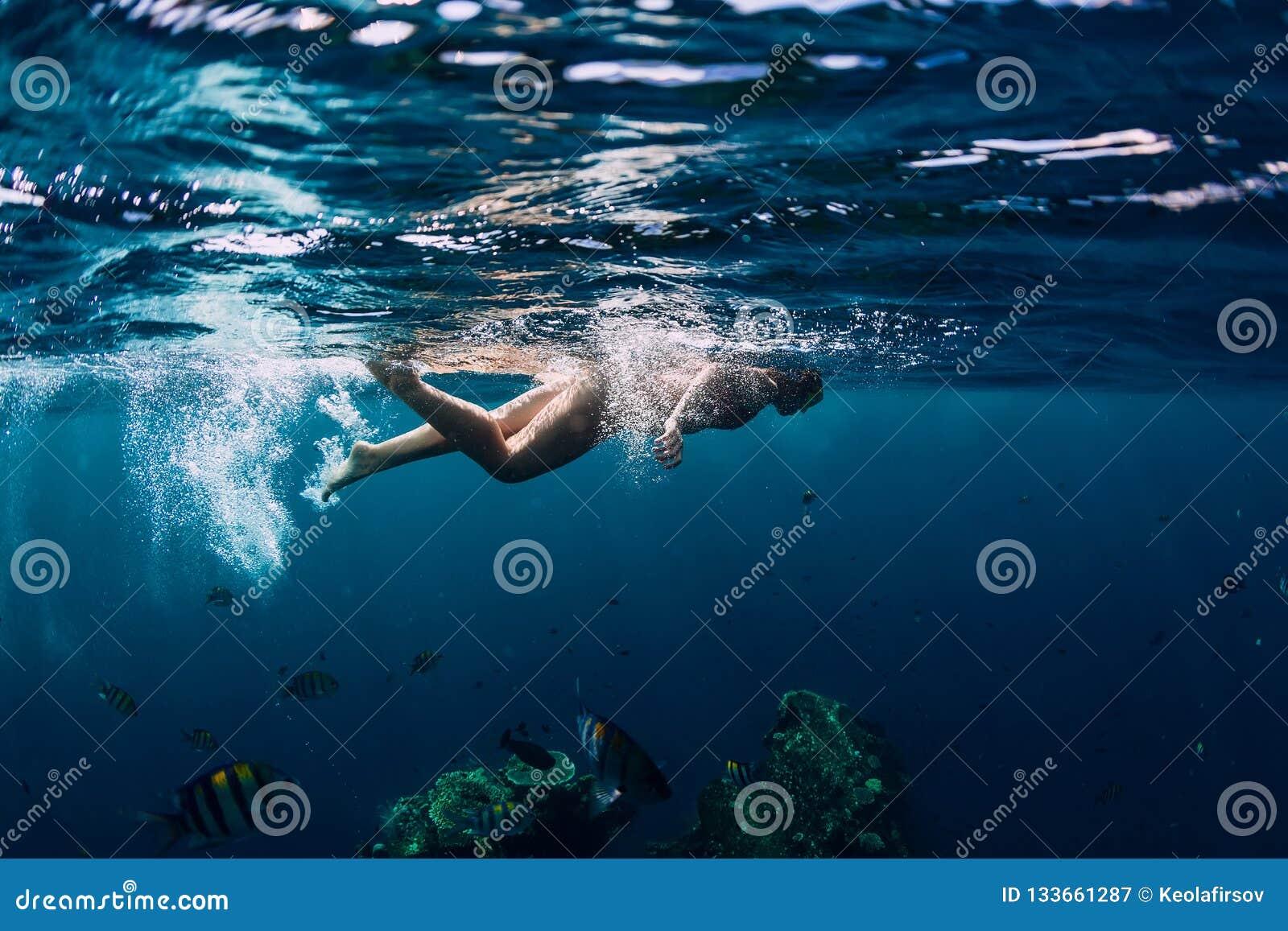 女子游泳在海难的热带海洋