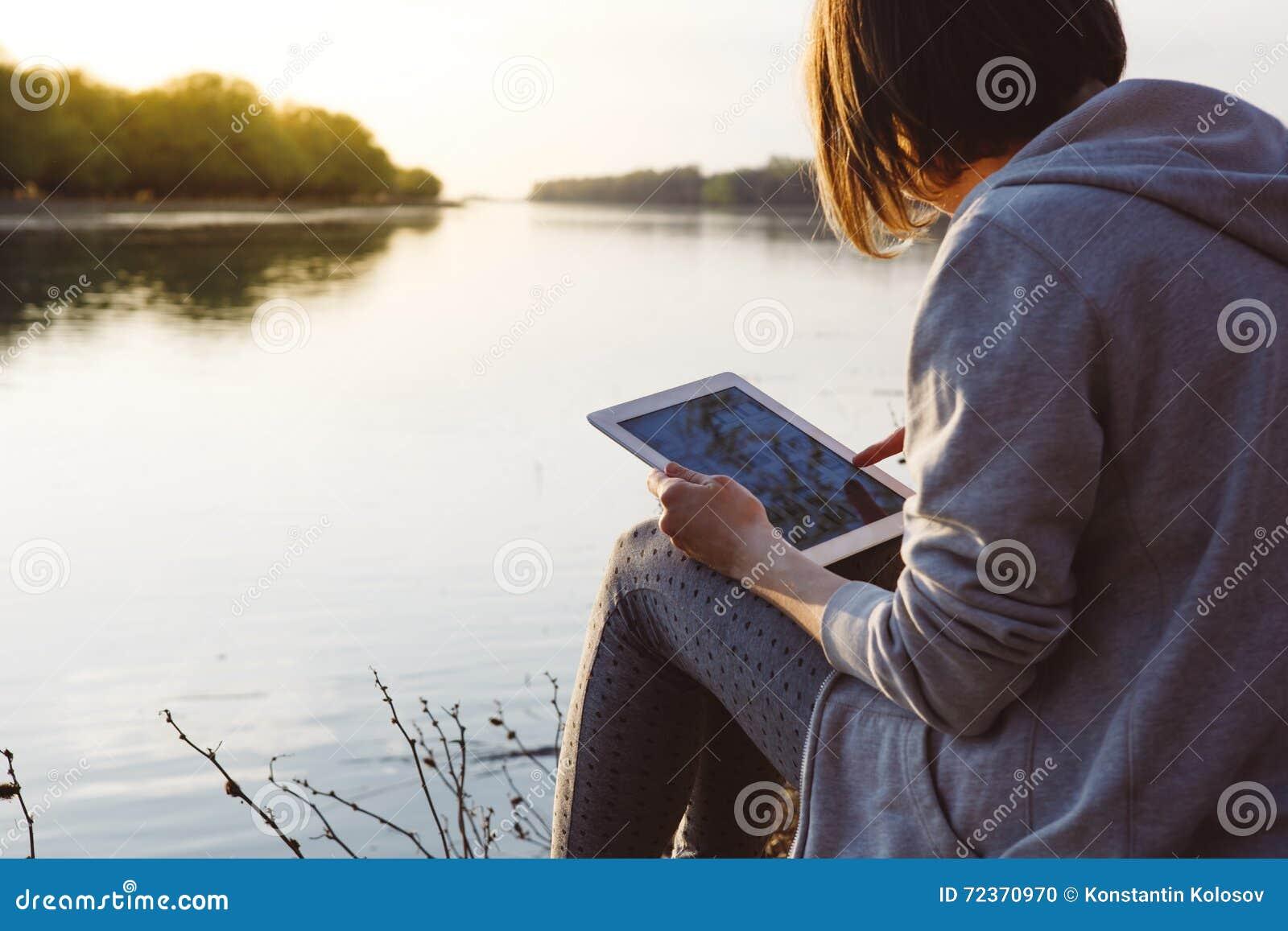 女孩与片剂一起使用在河