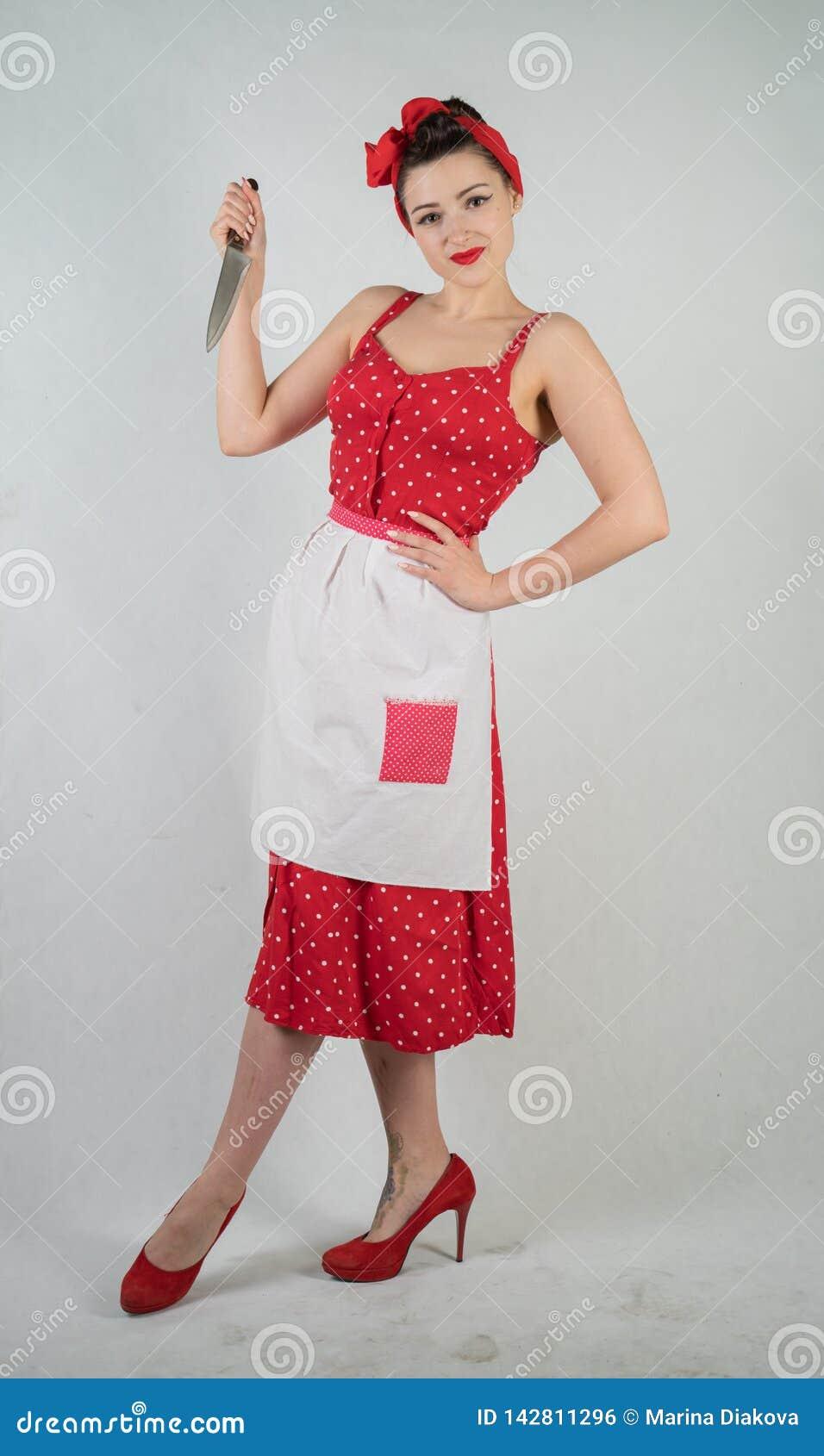 女孩主妇的危险别针红色葡萄酒圆点礼服的在她的手上站立与一把巨大的厨刀和愤怒高兴