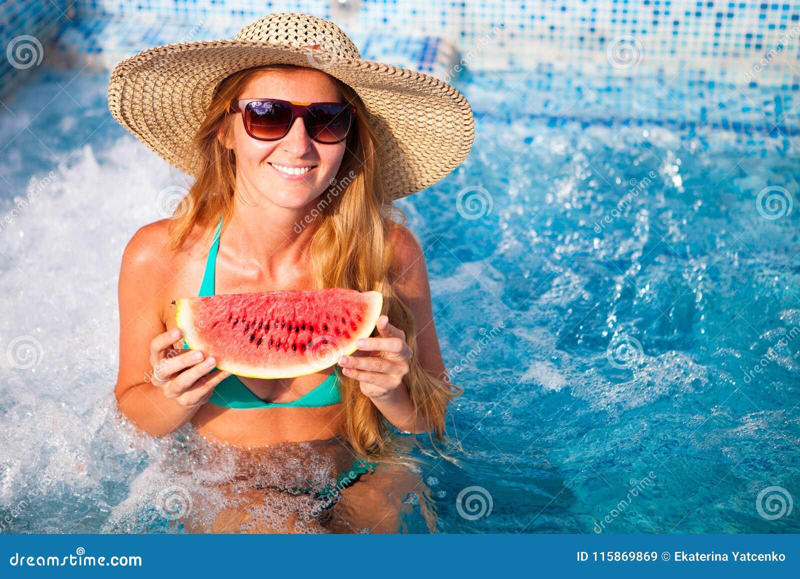 女孩举行一半在一个蓝色水池的一个红色西瓜,放松o