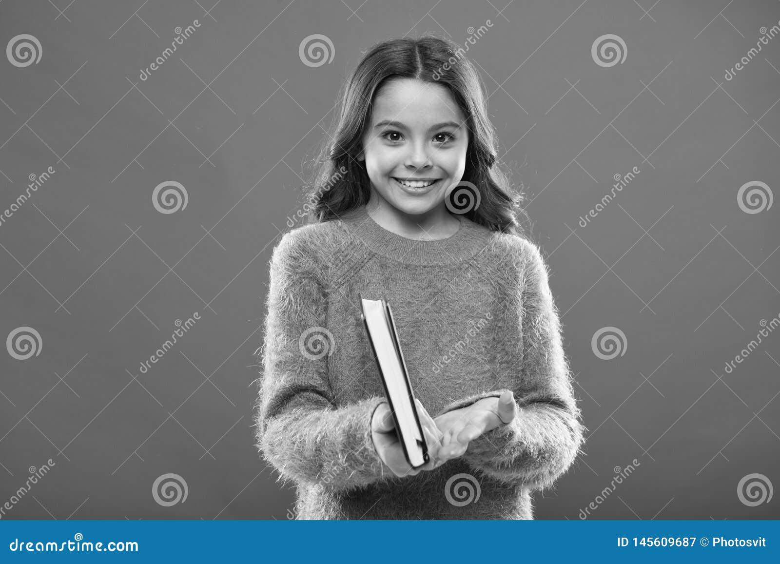 女孩举行书读了在橙色背景的故事 孩子享用看书 书店概念 美妙的自由的孩子的