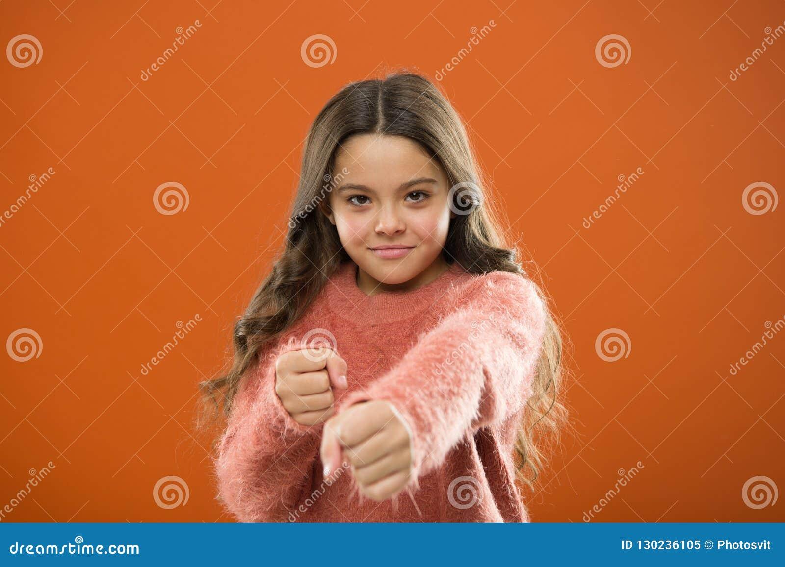 女孩举行拳头准备好攻击或保卫 坚强女孩的孩子逗人喜爱,但是 孩子的自卫 保卫无罪 怎么教