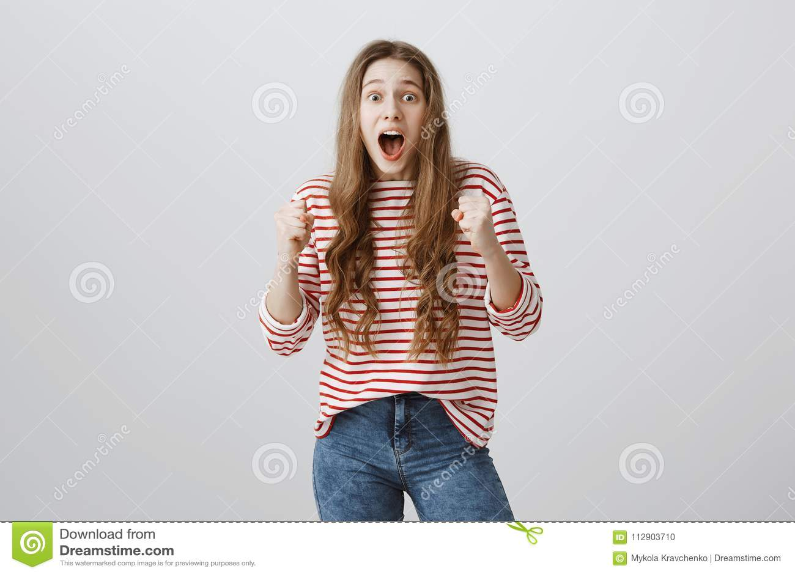 女孩从灌木跳的被惊吓朋友 相当站立与被举的握紧拳头的欧洲少年,喘气