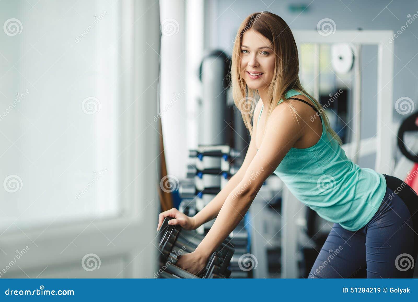 女子哑铃健身_在健身房的强的女子举重 解决与哑铃的妇女在健身房 哑铃由健身女孩