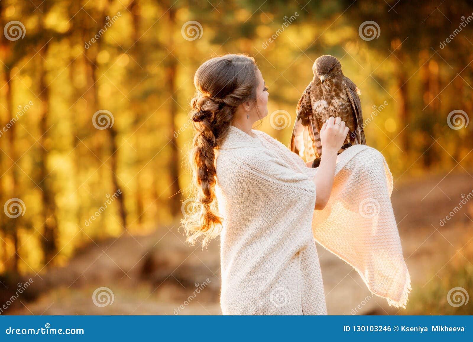 女孩冲程猎鹰坐她的在落日的光芒的手